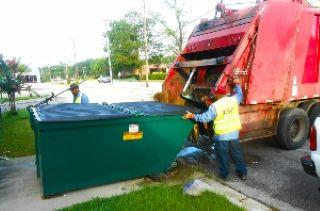 Man emptying dumpster into truck