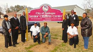 Senior Citizens Staff Around Sign
